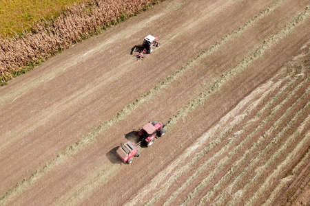 Areal view of two red Tractor baling hay