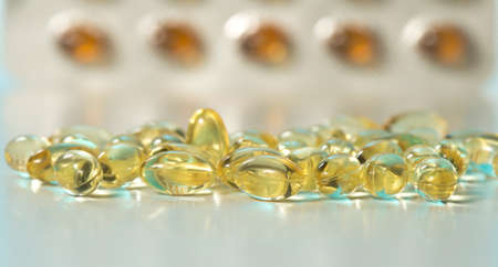Set of shiny yellow Vitamin D fish oil capsule on white background