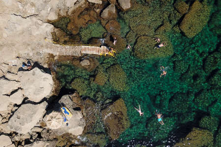 Top view on a rocky beach and turquoise sea with swimmers and snorkellis