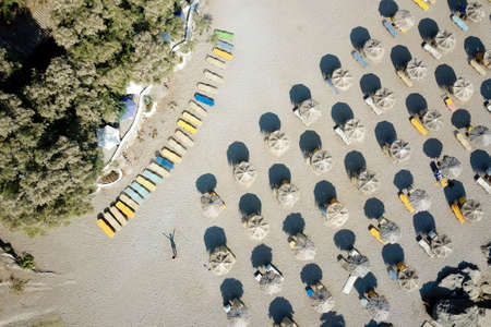 View from above on the Mediterranean sandy beach with umbrellas and sun beds