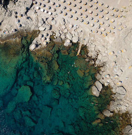Areal view on a rocky beach and turquoise sea with sunbeds and umbrellas 版權商用圖片