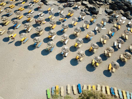 Top view on sandy beach with colorful sunbeds and parasols