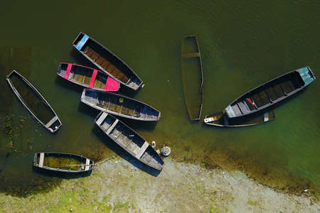 Top view on group of traditional colorful wooden fishing boats in lake