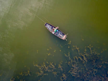 Areal view on angling fisherman in boat on river