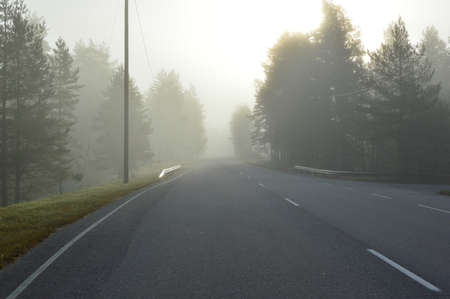 open road: Foggy open road in Finland, the sun is shining from behind a veil of fog.