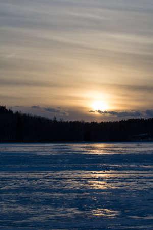 finnish: Finnish lake in winter evening. Sun is going down.