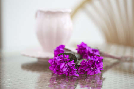 Violets on a lace napkin with a cup of coffee.