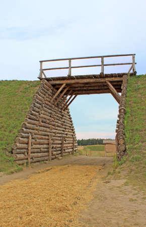 Entrance with bridge through hill Stock Photo