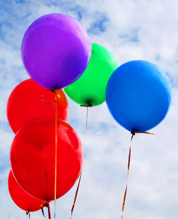 Coloured balloons floating in a cloudy sky photo