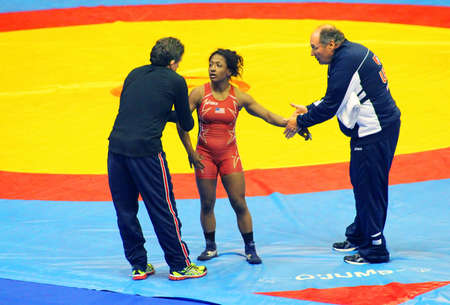 catch wrestling: KYIV, UKRAINE - FEBRUARY 16: Victoria Anthony (USA) rests with her coaches during 19 International Tournament in wrestling February 16, 2013 in Kyiv, Ukraine