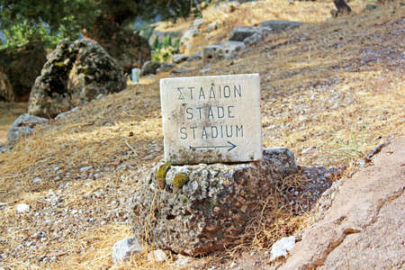 Pointer of ruins of  stage theater in Delphi, Greece photo