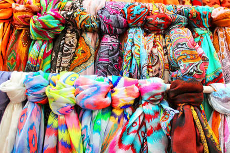 Rows of colourful silk scarfs hanging at a market stall in Tossa de Mar, Spaine Stock Photo
