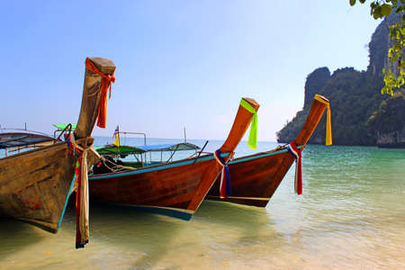 Holiday vacation concept - Long tail boats on tropical beach with limestone rock, Krabi, Thailand photo