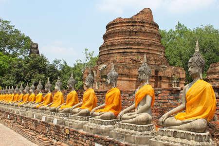 Aligned buddha statues with orange bands in Ayutthaya, Thailand photo