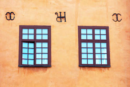 Windows of yellow iconic buildings on Stortorget, a small public square in Gamla Stan, the old town in central Stockholm, Sweden Stock Photo