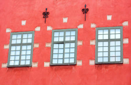 Windows of red iconic buildings on Stortorget, a small public square in Gamla Stan, the old town in central Stockholm, Sweden