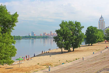 Unidentified people are resting on the beach of Dnipr river in Obolon district, Kyiv, Ukraine  Obolon embankment is a favorite place of people for resting in Kyiv
