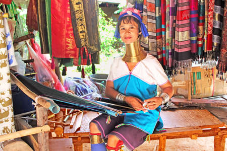 Unidentified Padaung  Karen  tribe woman weave on traditional device near Mae Hong Son, Thailand, Chiang rai, Karen Long Neck hill tribe village  Padaung women wear brass rings on the neck since the age of 5 years