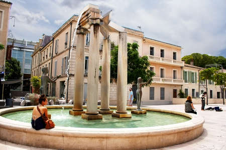 Unidentified tourists near fountain in Nimes, France