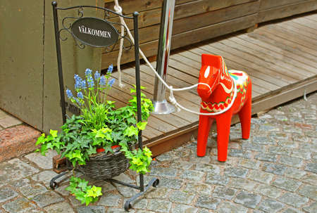 Inscription Welcome, flowers and a hand-made traditional wooden Dalecarlian Horse (symbol of Swedish Dalarna and Sweden in general) at the entrance to the little shop in Gamla Stan, Stockholm, Sweden
