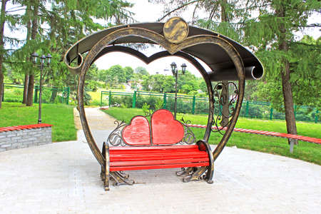 horizon over land: Wooden bench with back in the form of hearts, Kyiv, Ukraine Stock Photo
