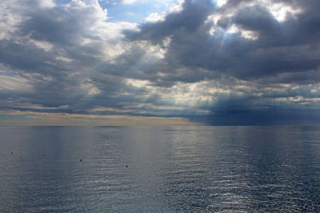Sun rays passing through the storm clouds over the sea photo