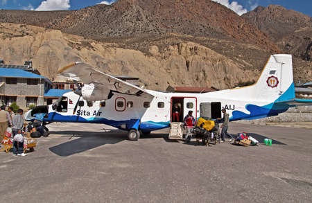 tara: Passengers arrived and unloaded luggage from the plane of Sita airlines at the Jomsom airport, Annapurna region, Nepal Editorial
