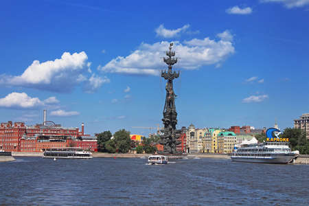 Floating pleasure boats with people near Peter the Great monument and Former confectionery factory building of the Red October in Moscow, Russia