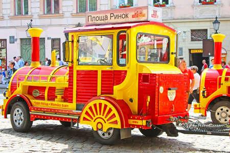 lviv: LVIV, UKRAINE - JUNE 29, 2014: Sightseeing car train  in the center of Lviv, Market square, Ukraine