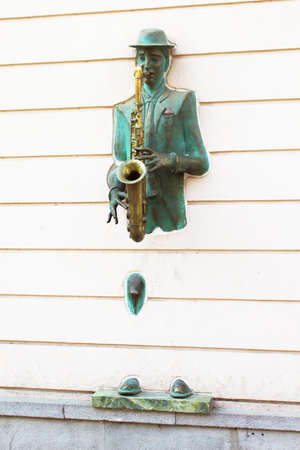 rustaveli: Bronze statue of saxophonist coming through the wall on Rustaveli street in old Tbilisi, Georgia