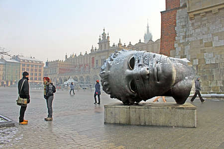 Head sculpture Eros Bendato on Market Square by polish artist Igor Mitoraj with Sukiennice cloth hall on background