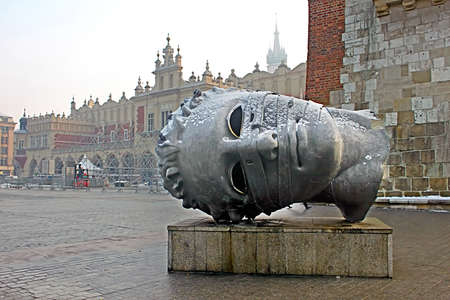 Head sculpture Eros Bendato on Market Square by polish artist Igor Mitoraj with Sukiennice cloth hall on background