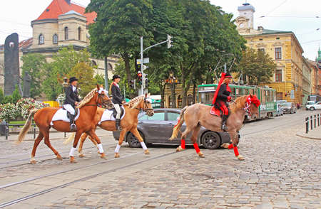 Cortege with riders on horseback on the streets in historical city center, Lviv, Ukraine Editorial