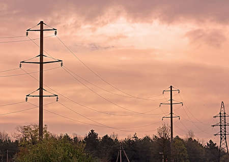 electric grid: Landscape of power lines for electricity metal towers and sunrise