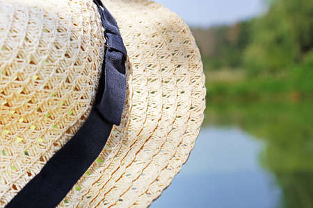 Straw hat on the lake and forest background