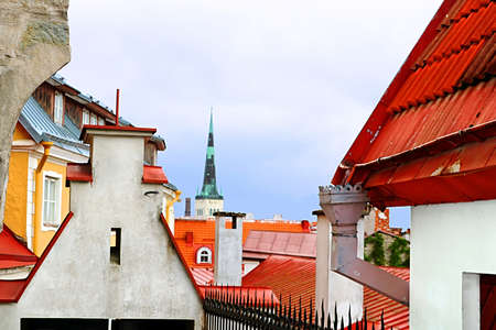 View of bell tower of the Church of St. Nicholas and bright roofs in Tallinn, Estonia Stock Photo