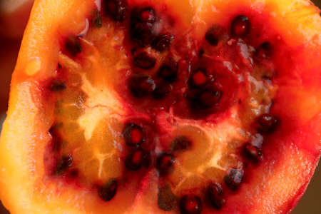 Ripe tamarillo fruit meat close-up cross-section texture as a backdrop composition