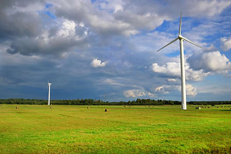 Wind generators turbines on summer landscape, blue sky, green grass and corps field, rainy weather, Latvia Stock Photo