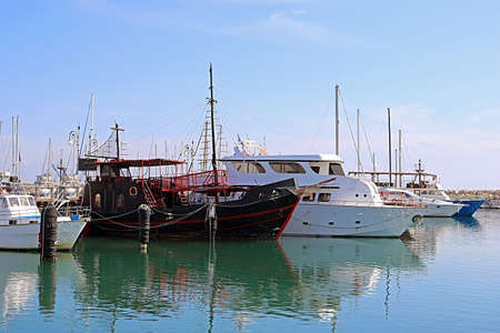 Yachts in Larnaca port, Cyprus. One black boat is different from the others - it looks like a pirate ship