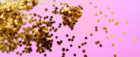 Delicate pink background with golden glitter stars. Flat lay. Holiday concept. New year time. Banner