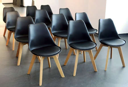 Minimalist Scandinavian design of conference room. Rows of black chairs in meeting room. Seats for participants