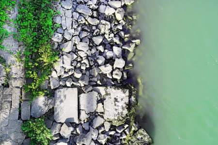 Top view of the rocky shore of the river and water, green plants. Edge of water and large boulders. Copy space 版權商用圖片