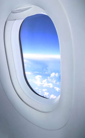 View of clouds through the aircraft porthole. Aircraft window. Travel concept Banco de Imagens