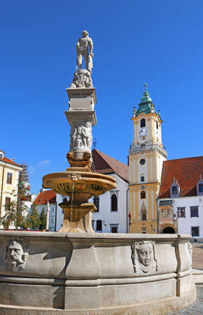 View of Roland Fountain and Old town hall at Main Square Hlavne namestie in Bratislava Old Town, Slovakia. The fountain was constructed in 1572 for supplying citizens of the city with water