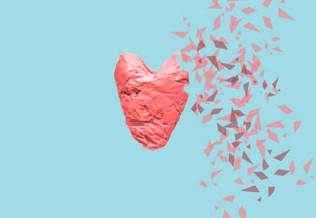 Delicate red heart made from crumpled paper partially torn to pieces on a gentle trendy blue background. The concept of fragility of the human heart. Medicine