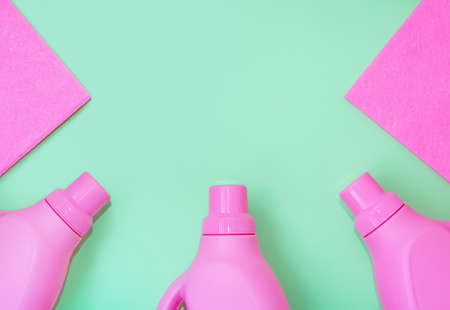 Pink plastic bottles with chemicals for cleaning, rags for cleaning. Delicate green background. Cleaning concept Imagens