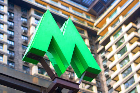 KYIV, UKRAINE - JULY 04, 2020: Green metro sign and modern building as background