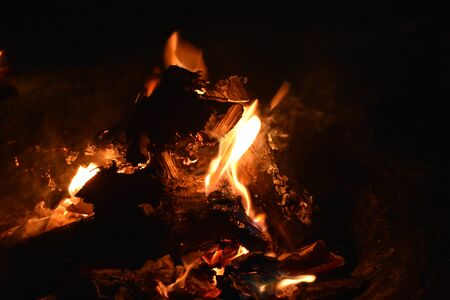 Molten embers and logs in dying campfire