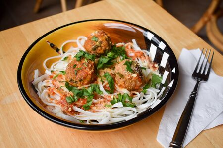 Rice noodle spaghetti and meatballs on wood background with white napkin and fork on the side