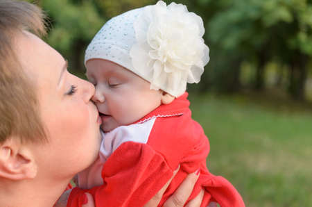 tenderly: Loving mother tenderly kissing her child with affection. Stock Photo